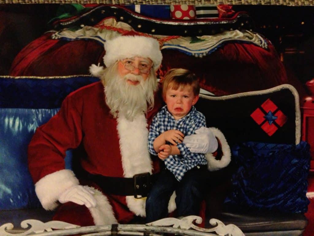 Boy-sitting-on-santa