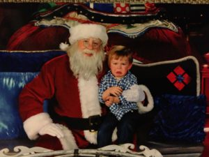 Boy-sitting-on-santa