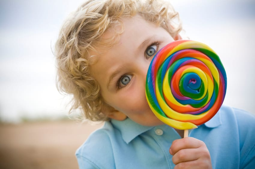 Young blonde boy peeks out from a colorful lollipop