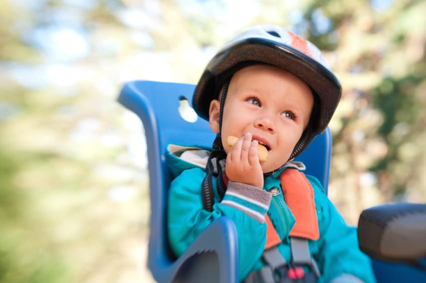 Little boy in bike child seat eating cracker outdoors in motion blur by lensbaby