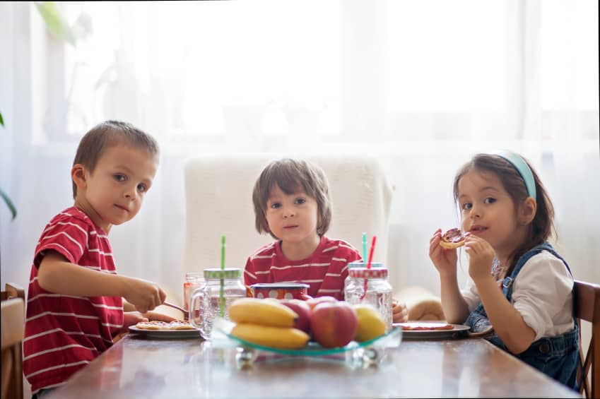Three happy kids, two brothers and little sister, having healthy breakfast sitting at wooden table in sunny kitchen