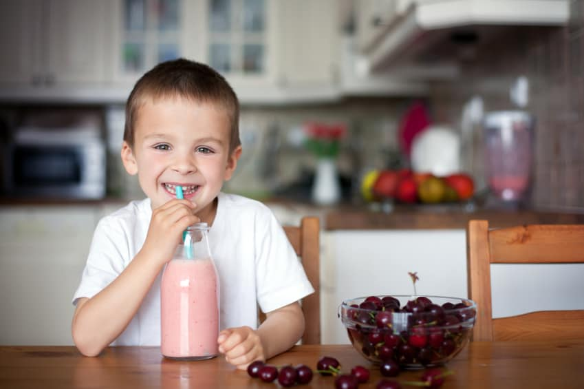 Happy school boy drinking healthy smoothie as a snack at home, cherries in a bowl on the table