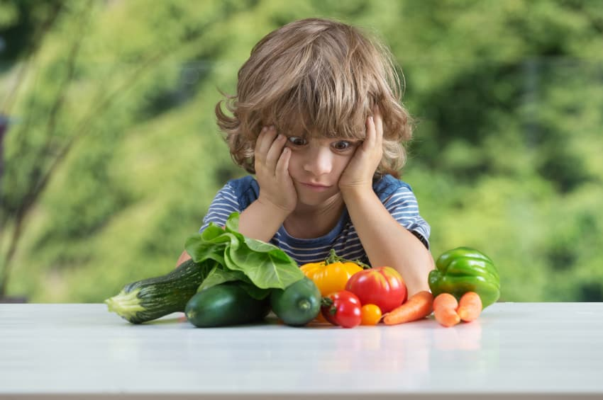 overwhelmed child staring at vegetables, refusing to eat them