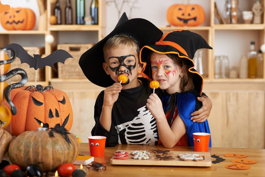 Brother and sister dressed in Halloween costumes eating Halloween candy and homemade treats