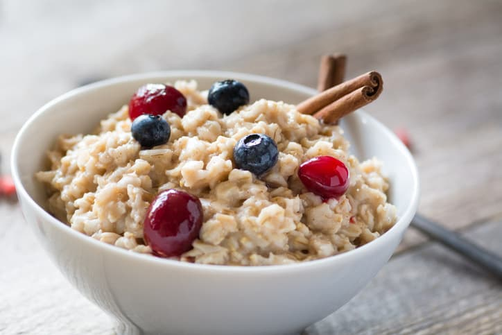 bowl of oatmeal with fruit and cinnamon