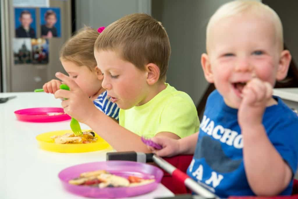 Three kids of varying ages feeding themselves at the table. Each one uses their own plates and utensils.