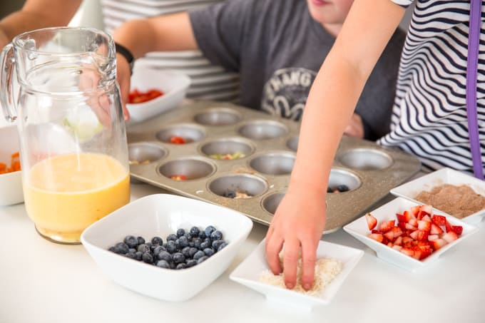 kids assembling easy egg bites in muffin tins with fruit
