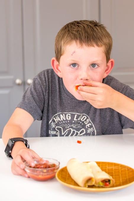 Kid eating breakfast taquitos