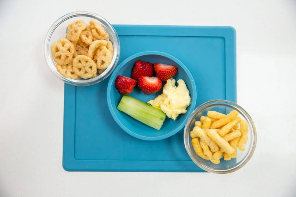 flat lay view of baby finger foods including puffies, cut up strawberries, cucumber
