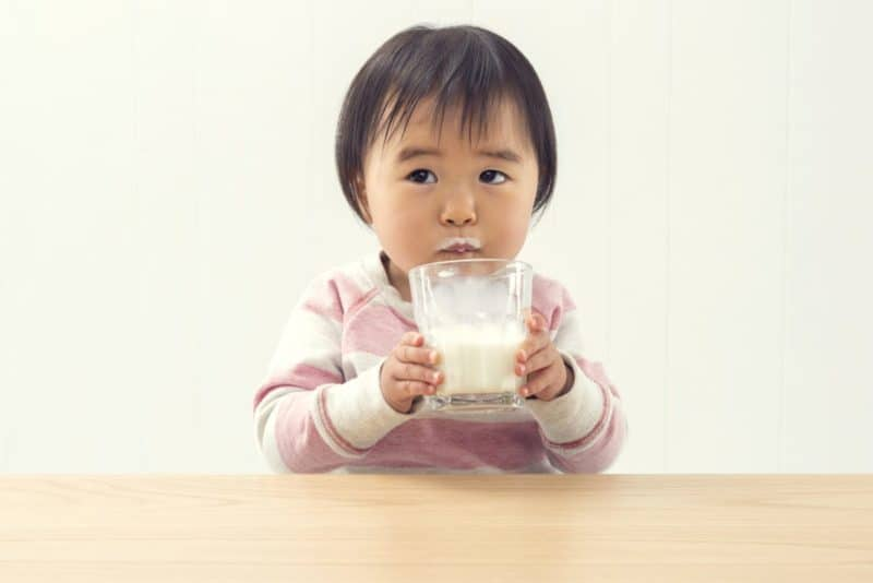 toddler holding a glass of milk while looking at the camera