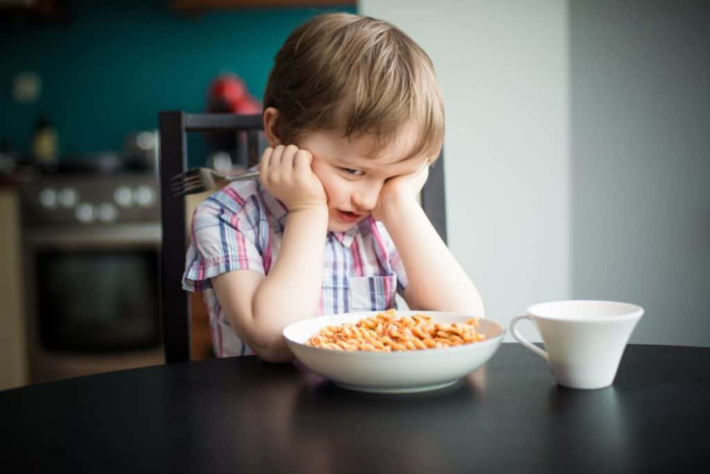 frustrated child sitting in front of meal, refusing to eat