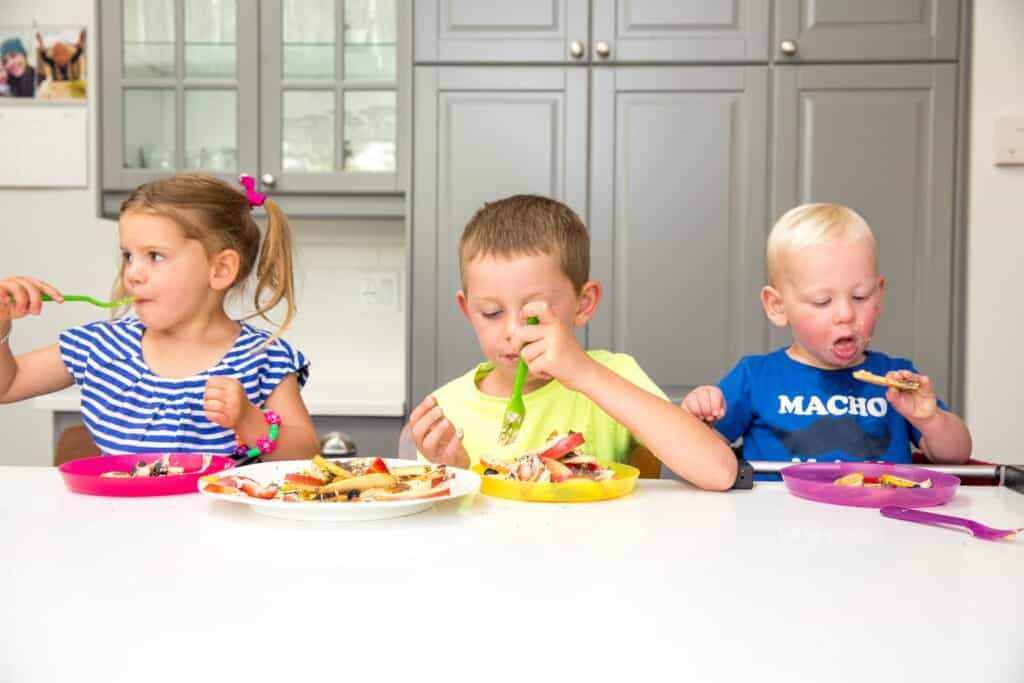 three children eating snacks