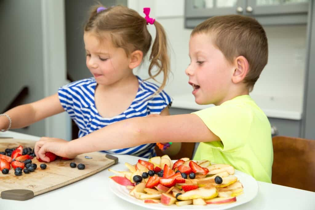 kids putting together a plate of sliced apples, blueberries and strawberries