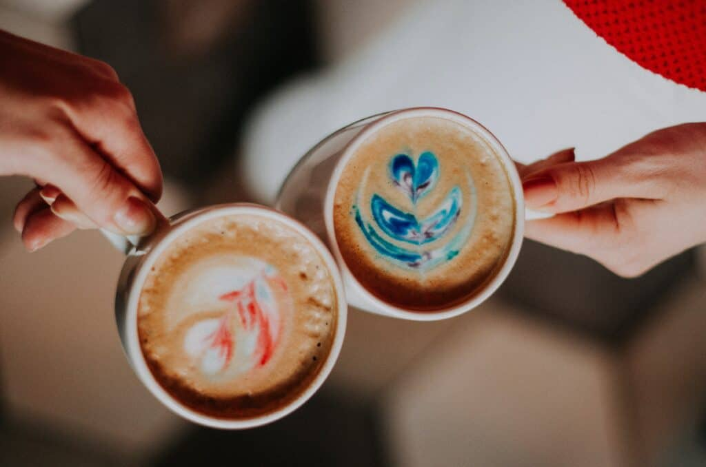 two cups of fancy lattes touching one another. One latte is coloured pink, the other is coloured blue.