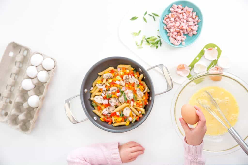 top down image of frying pan with pasta, eggs, vegetables