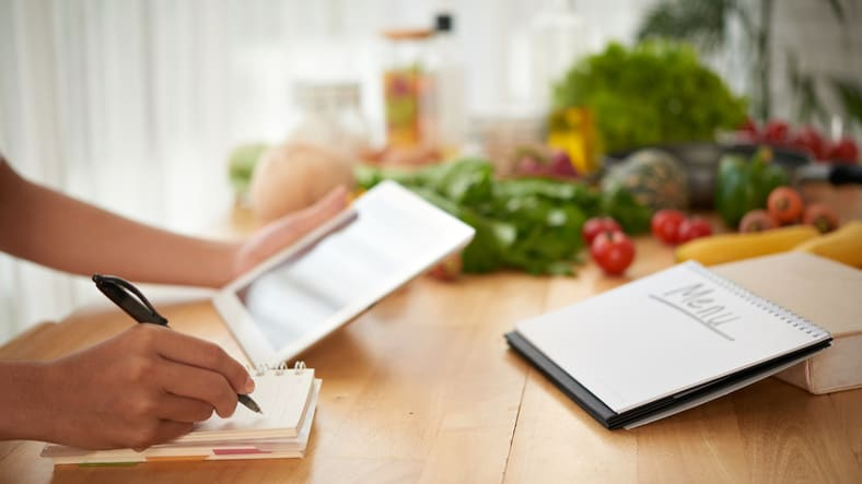 Hands of woman composing healthy menu for upcoming week