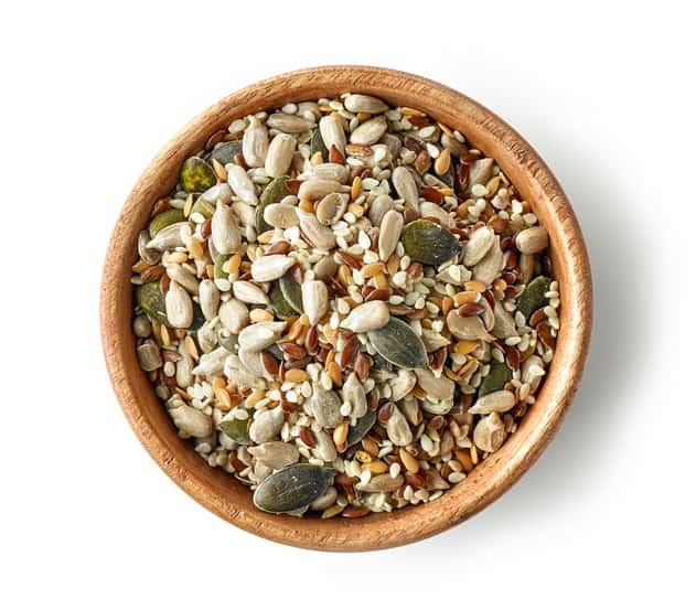 mix of seeds in wooden bowl isolated on white background, top view