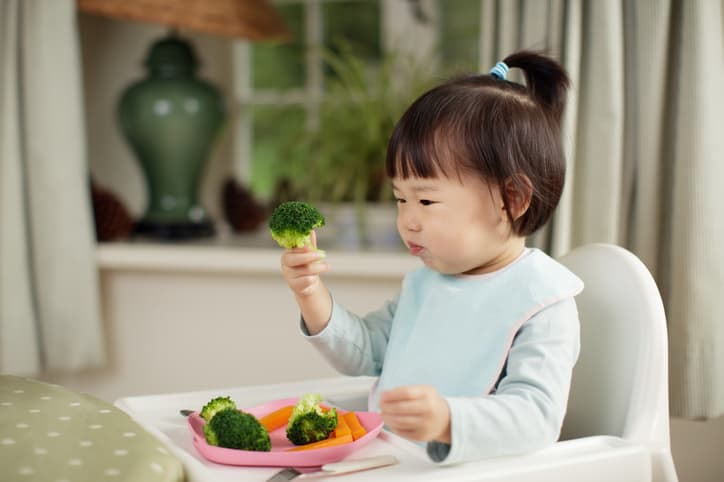 baby holding up pieces of broccoli with interest