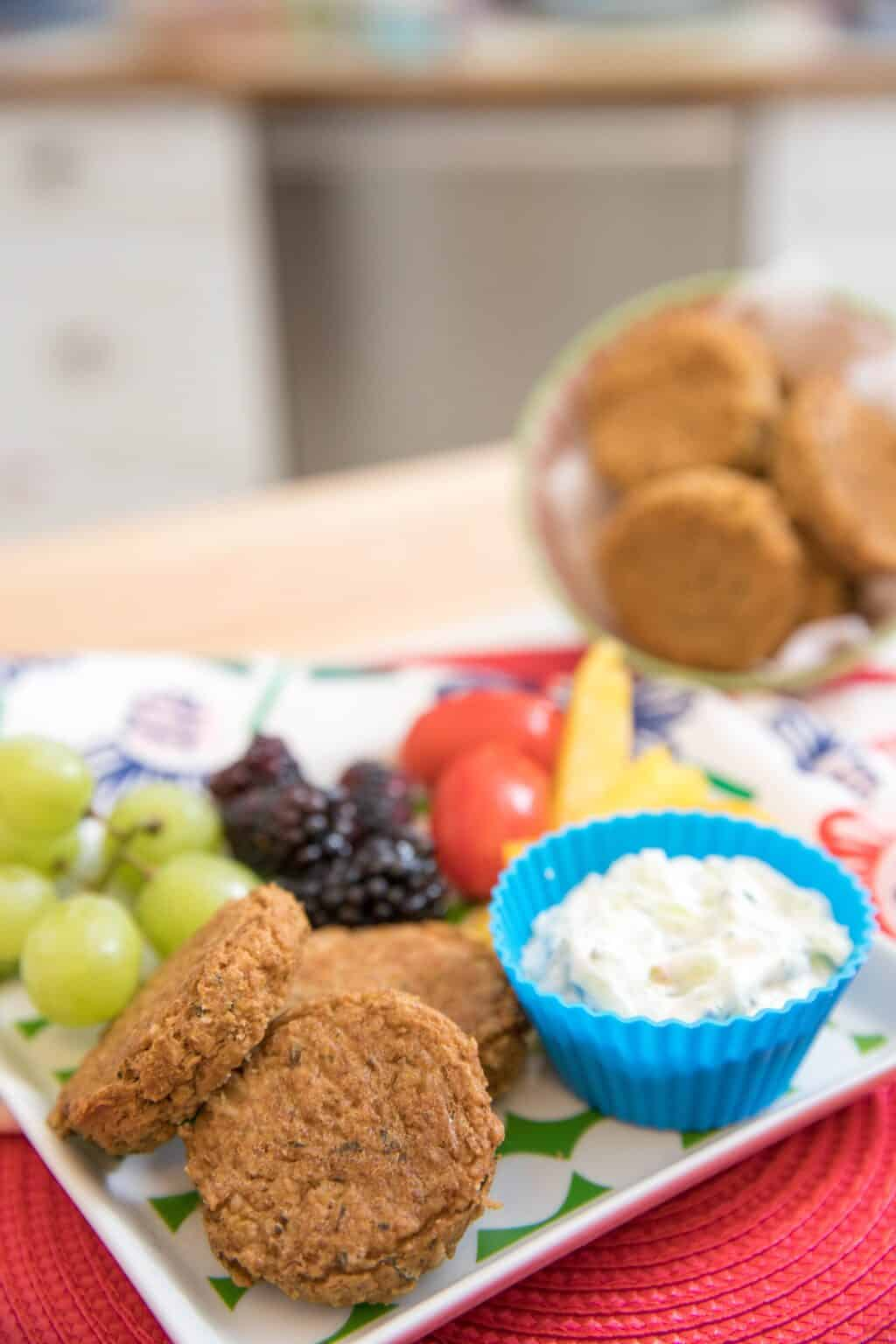 vegan lentil nuggets served with dip and a plate of fruits and vegetables