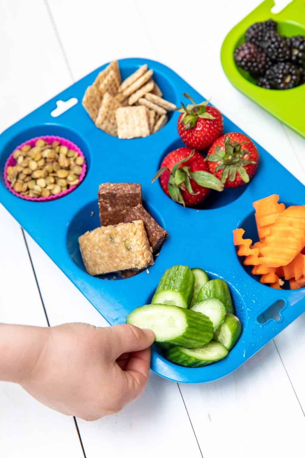 snack board with assortment of fruit, cheese, nuts and seeds
