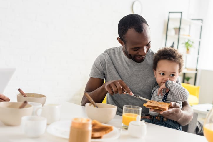 dad holding baby while introducing baby to peanut butter on toast