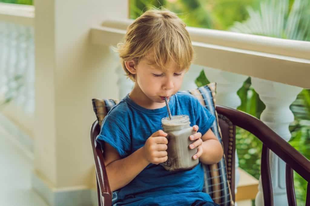 a boy drinks a protein-rich smoothie from a straw
