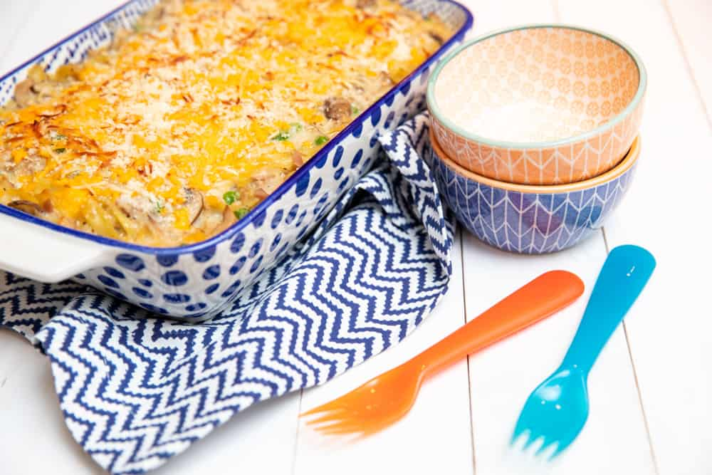 tuna noodle casserole in casserole dish with an assortment of utensils and bowls