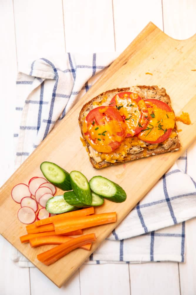 tuna melt with tomatoes cheese and chives with a pile of fresh cut vegetables including cucumber radish and carrots