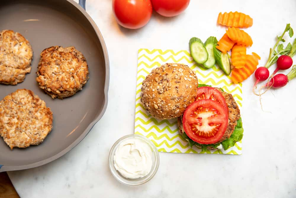 tuna patties in a skillet with a side of assembled burgers with lettuce tomatoes and sauce
