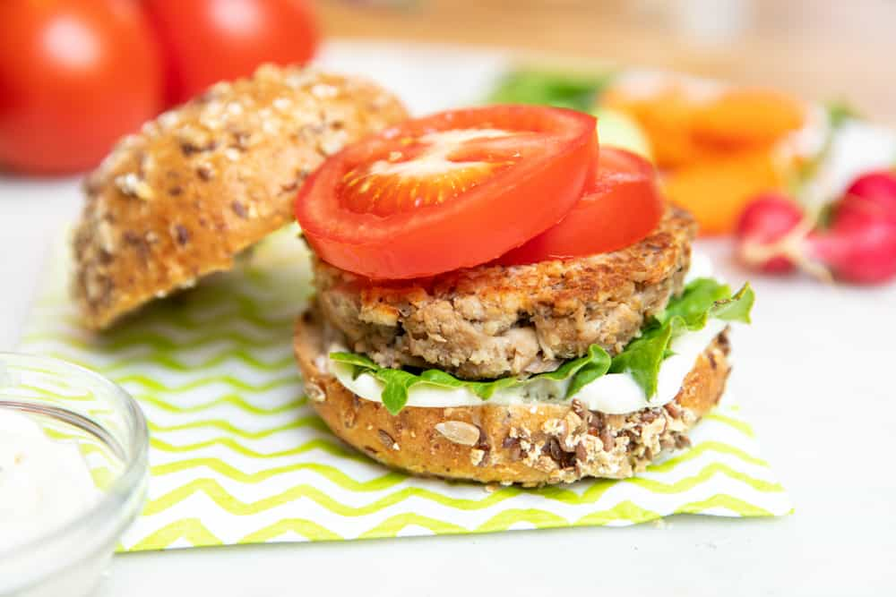 tuna burgers on a seedy bun with tomatoes, lettuce and sauce