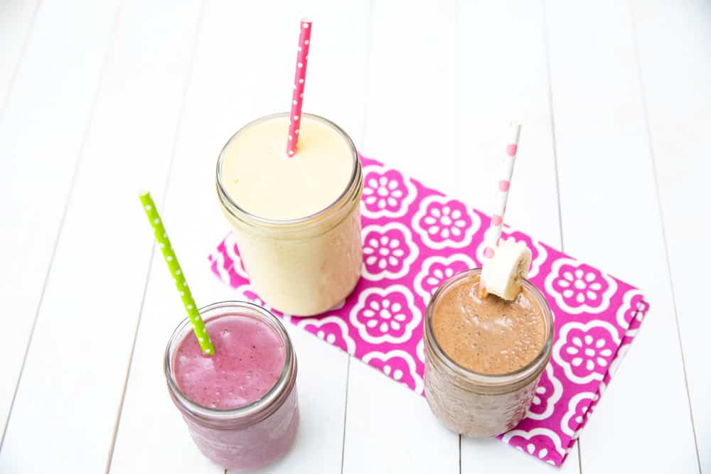 various smoothies in jars on a white textured background with pink napkins