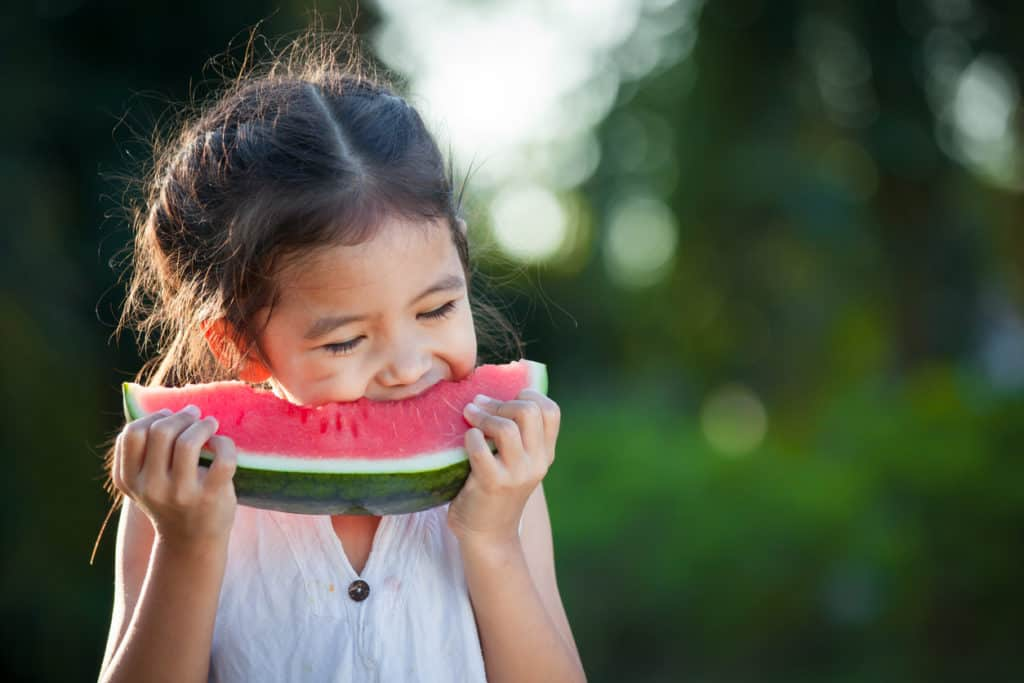 Cute little child girl eating watermelon fresh fruit in the garden