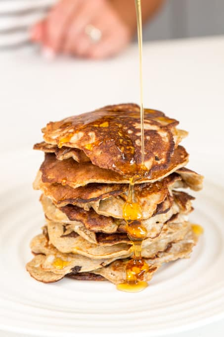 syrup drizzling over stack of pancakes