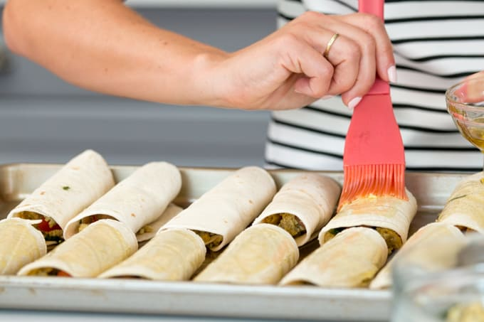 brushing egg wash over taquitos on a baking tray