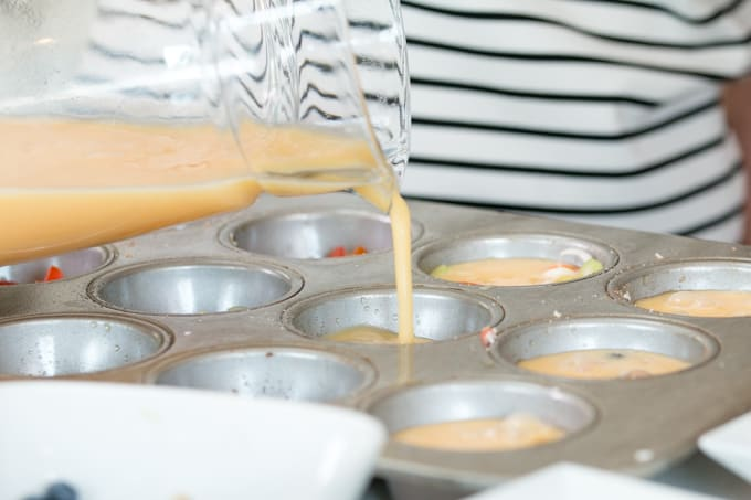 egg mixture being poured into muffin tins